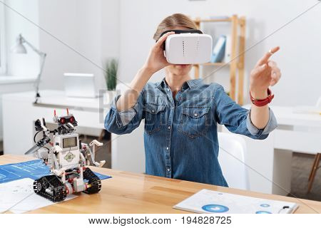 Full of interest. Concentrated confident skilled volunteer sitting in the lab and using visual reality glasses while interacting with electronic robot