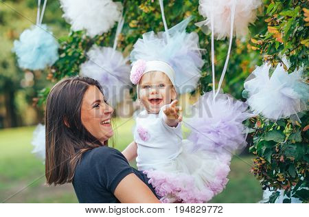 Beautiful mother and her little daughter outdoors. Nature. Beauty Mom and her child are playing in the park together. Mom and the child.
