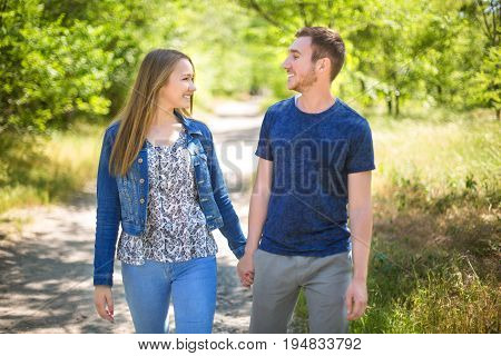 A cute couple in casual clothes is hugging and looking at each other in a park. Young couple holding hands and looking at each other outside. Charming couple loving each other outdoors.