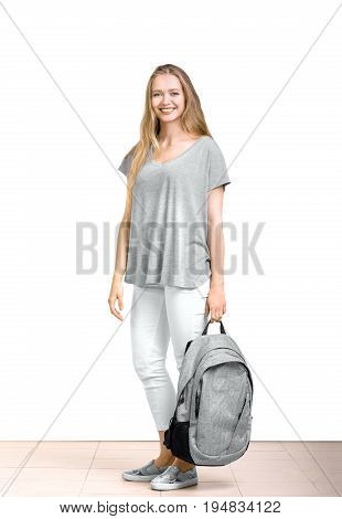 Full length image of young and charming girl, isolated on a white background. Attractive and beautiful girl with long blond hair and in casual gray clothes holds a backpack in her hand and smiles cutely.