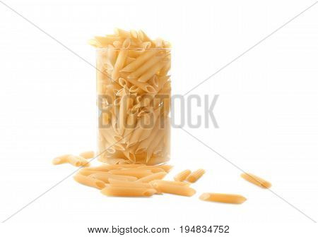 Raw and bright yellow pasta in a huge transparent glass, isolated on white background. Pasta, macarons, noodle, spaggeti in a glass. A huge glass full of raw and bright Italian food pasta.