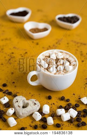 Cup of coffee with marsh-mallows on yellow background. There are little heart-shaped bowls filled with coffee beans and cinnamon on a background behind the cup.