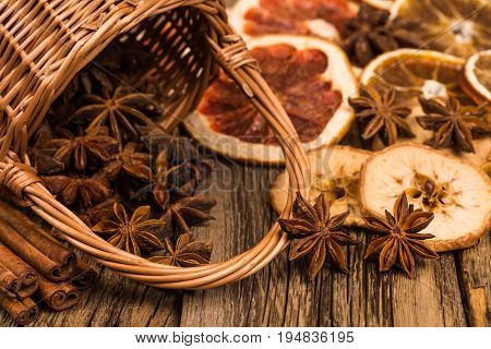 Star anise in a wicker basket on an old wooden table. Selective focus.