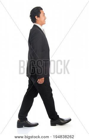 Full length side view of happy young Southeast Asian businessman walking, isolated on white background.
