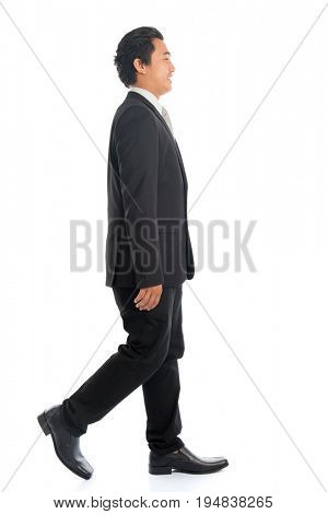 Full length side view of attractive young Southeast Asian businessman walking, isolated on white background.
