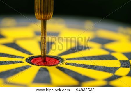 Selective focus on gold needle dart in the center of dartboard as Business goal or target concept.
