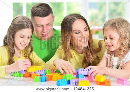Portrait of a happy family collecting colorful blocks together