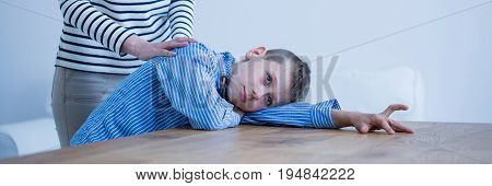 Autistic boy lying on desk being comforted by his therapist