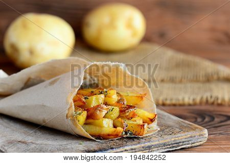 Fried potatoes with spices. Homemade fried potatoes in paper and on a wooden table. Potato snack recipe. Country style