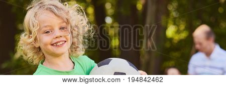 Young kid with soccer ball in the park during summer