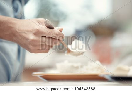 Woman hand holding spoon with rice-milk. Horizontal photo