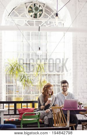 Young couple of freelancers working in industrial interior with big window