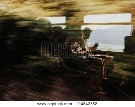 Milan Italy - June 13 2017: blurred image of passengers in train reading a book