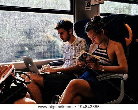 Milan Italy - June 13 2017: young man and girl passengers on train reading a book