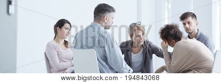 Rehab group sitting in a circle with therapist comforting woman
