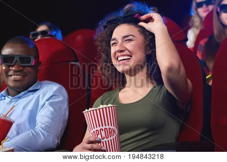 Beautiful young woman laughing happily while enjoying a movie with her friends at the local cinema positivity recreation emotions comedy laughter hilarious concept.