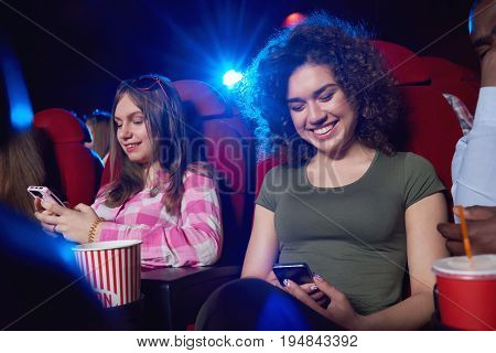 Young cheerful women smiling using their smart phones while sitting at the cinema auditorium watching a movie technology mobility connection communication friendship youth entertainment activity.