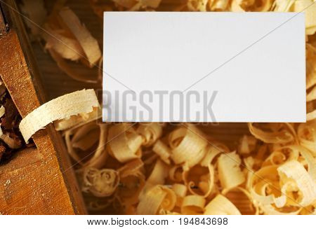 Blank business card on wooden table for carpenter tools with sawdust top view.