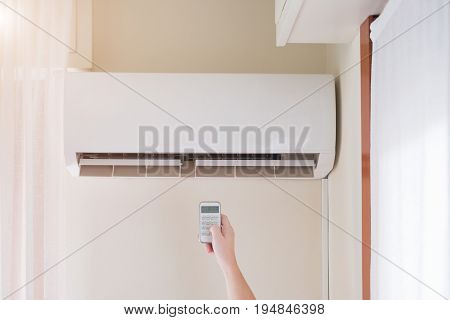 Air Conditioner And Hand With Temperature Remote Control
