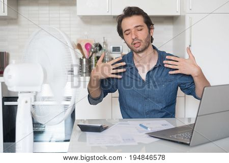 Sweaty Man Trying To Refresh From Heat With Fan