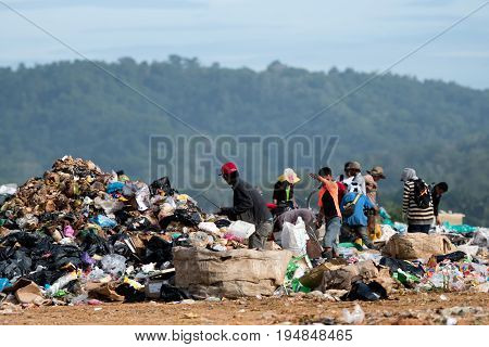 KOTA KINABALU MALAYSIA - 09 JULY 2017: People looking through rubbish on landfill site in Sabah Borneo. They scavenge here daily for useful items that can be resold and recycle.