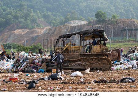 Kota Kinabalu, Malaysia - 09 July, 2017: Scavenger And An Aged Bulldozer  Pushing A Garbage At Landf