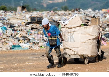 KOTA KINABALU MALAYSIA - 09 JULY 2017: Man pulling a big basket full of recyclable items at landfill site in Sabah Borneo.