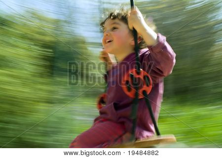 smiling boy on a swing with motion blur