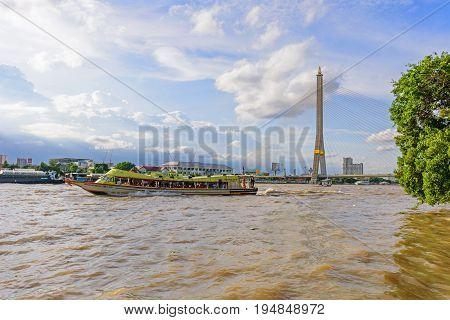 Bangkok , Thailand - 7 July, 2017 : Ferry boat for travel in Bangkok and RAMA 8 bridge in behind / RAMA VIII bridge