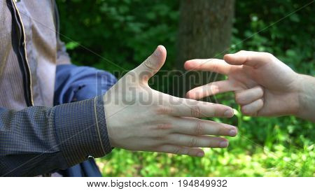 Rock scissors paper is played by two young man in the forest high definition video. slow motion