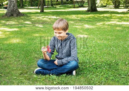 Boy playing with spinner while sitting on the grass