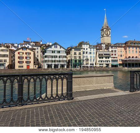Zurich, Switzerland - 18 June, 2017: old town buildings along the Limmat river, clock tower of the St. Peter Church. Zurich is the largest city in Switzerland and the capital of the Swiss canton of Zurich.