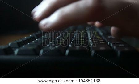 human hands working on the keyboard, dark room.