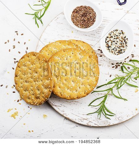Thin crispy grain breads for breakfast with flax seeds and sesame seeds on a light background. Top View