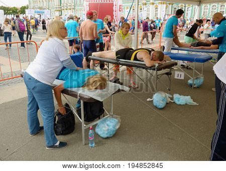 09.07.2017.Russia.Saint-Petersburg.Sports massage therapists help athletes after a marathon race.