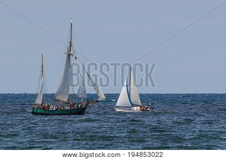 SAILBOAT - A small boat and gaff ketch are passing by the sea