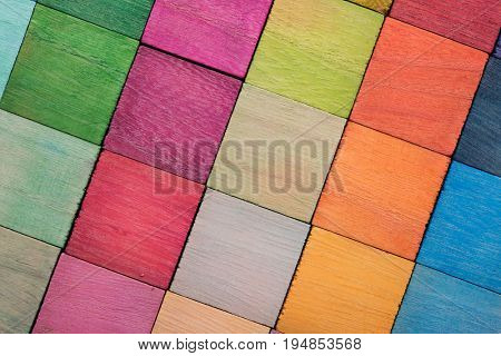 Spectrum of multi colored wooden blocks aligned. Background or cover for something creative or diverse. Transparent colors.