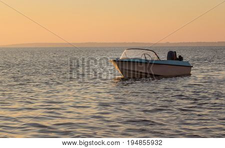 A lonely boat on small waves without a driver under a warm evening sky
