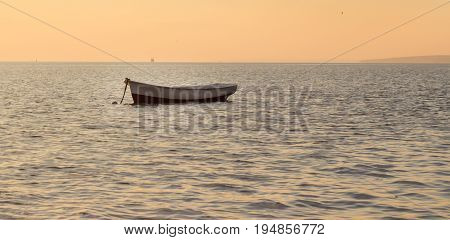 Lonely boat tied into the sea very beautiful evening soon sunset