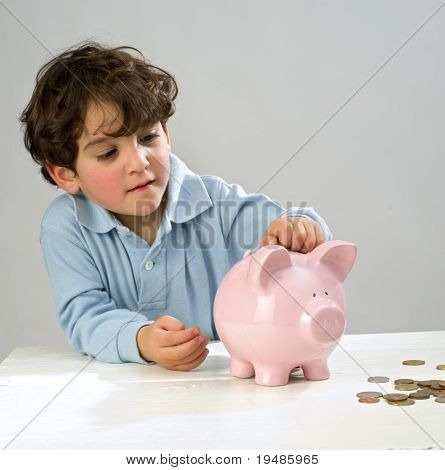 boy inserting a coin in a piggy bank