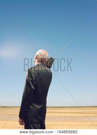 Rear view of businessman listening music on radio in desert