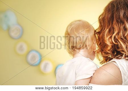 mother with a baby in her arms with her back to the camera.
