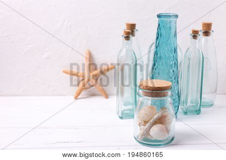 Ocean or sea theme home decorations. Decorative bottles starfish shells on white textured background. Selective focus. Place for text.