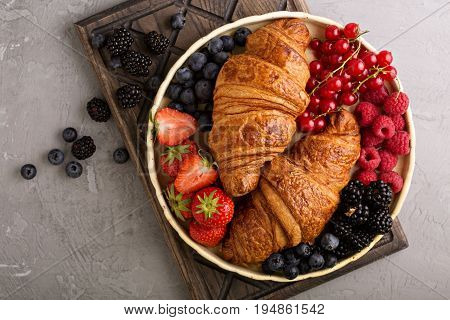 Healthy breakfast with freshly baked croissants and fresh berries overhead shot