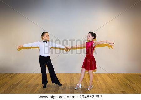 The young boy and girl posing at dance studio on gray. The ballroom dancing concept