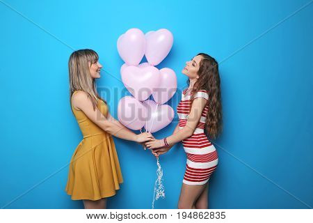 Two Young Woman With Pink Heart Balloons On Blue Background