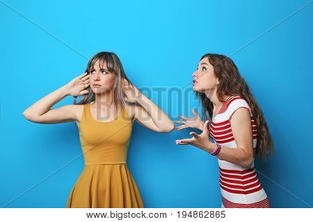 Two young woman having an argue on blue background