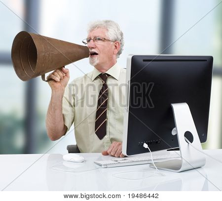 senior businessman using a retro megaphone in front of computer