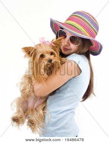 Young girl with sunglasses and hat, holding a Yorkshire terrier dog