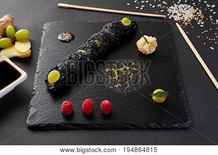 Sushi roll with crab on black shale. Roll with Grape, ginger, raspberry and soy sauce